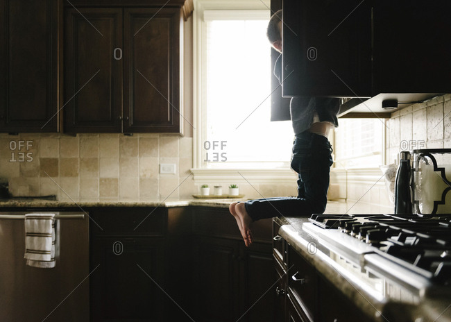 Boy searching something in cabinet while kneeling on kitchen counter at home
