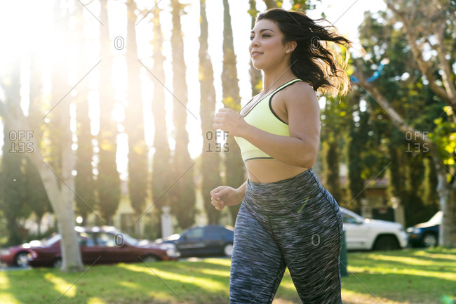 Woman jogging in park during sunny day
