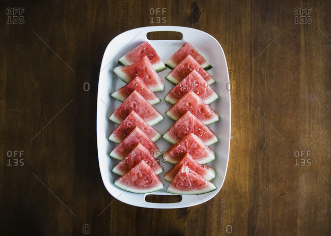 Overhead view of watermelon slices served in tray on wooden table