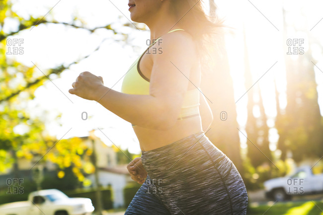 Midsection of woman jogging in park during sunny day