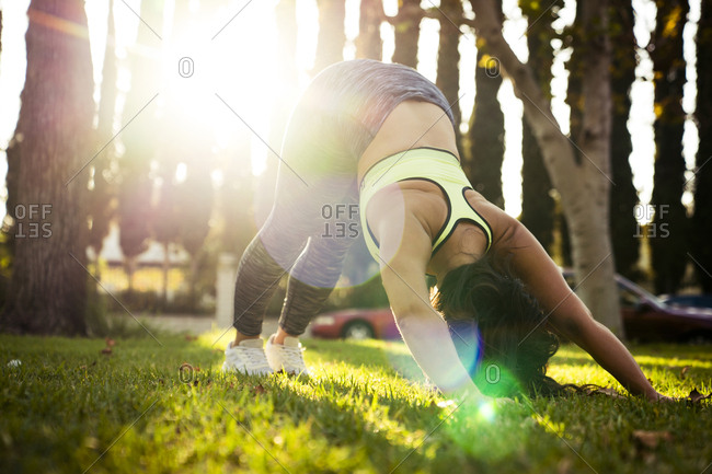 Woman practicing downward facing dog position in park during sunny day