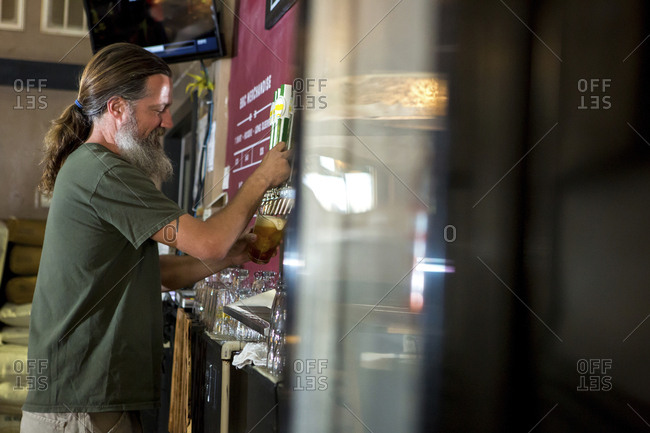 Side view of bartender pouring beer from tap
