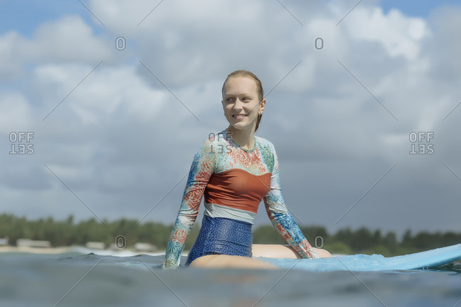 Smiling woman looking away while sitting on surfboard in sea against cloudy sky