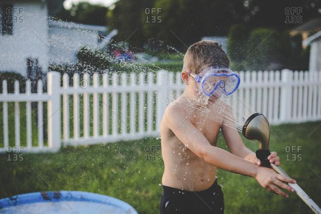 Playful shirtless boy wearing swimming goggles while spraying hose on him at yard