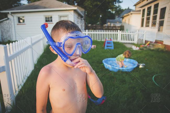 Shirtless brother wearing snorkel while sister playing in wading pool at yard