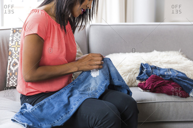 Midsection of woman stitching textile patch on jeans while sitting on sofa at home