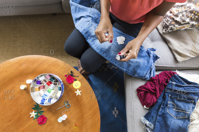 High angle view of woman removing thread from spool while sitting on sofa at home