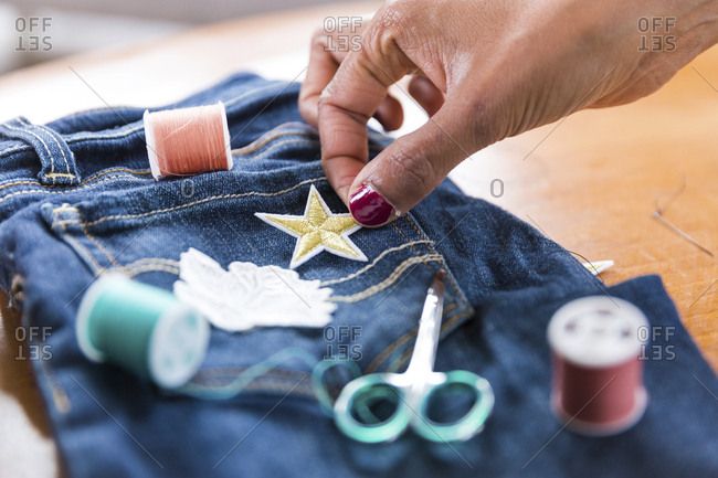 Cropped hand of woman putting star shape textile patch on jeans at table