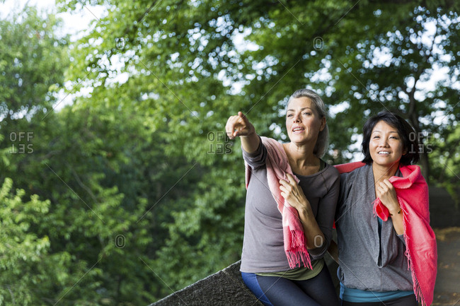 Woman pointing on something while leaning by friend on footpath against branches