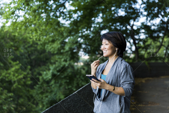 Happy woman talking on smart phone while using earphones on footpath against branches