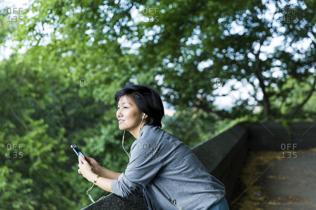 Thoughtful woman listening music while leaning on retaining wall against branches