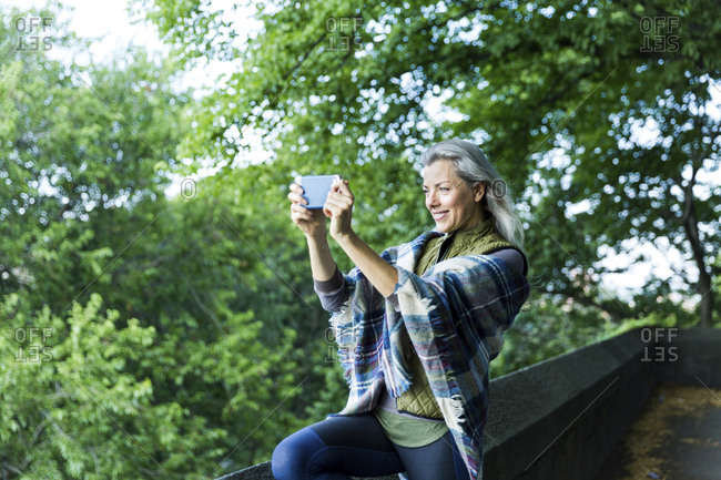 Woman photographing through smart phone while standing on footpath against branches