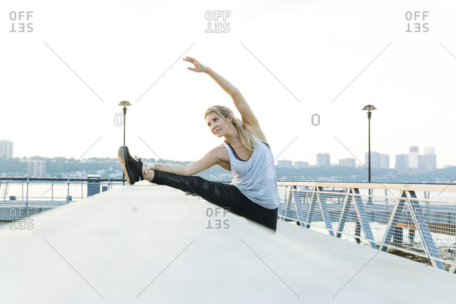 Woman stretching leg on railing at bridge against clear sky in city