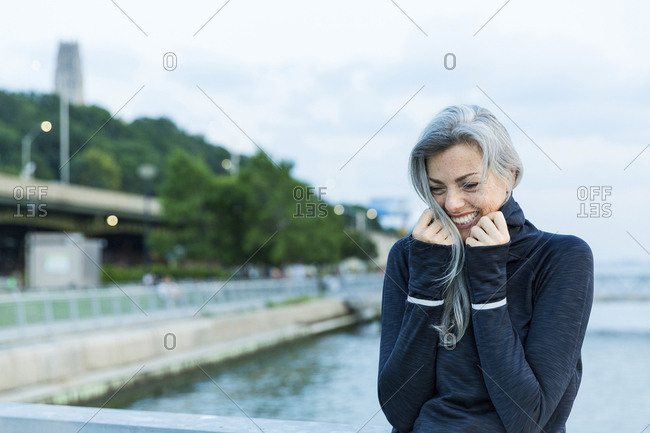 Cheerful woman in hooded shirt against sea on bridge
