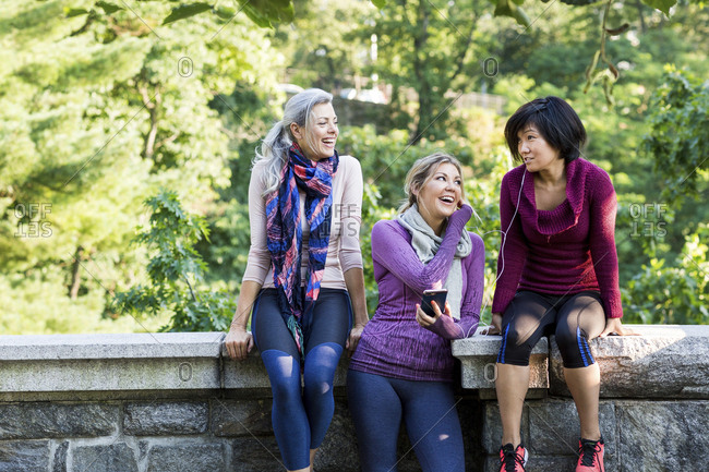 Happy women looking at friend sitting on retaining wall in park