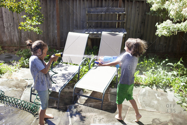 High angle view of playful brothers playing with water in yard during sunny day