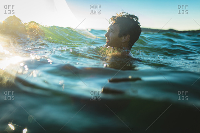 Happy man swimming in sea against sky