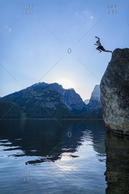 Low angle view of teenage boy cliff jumping into river against sky