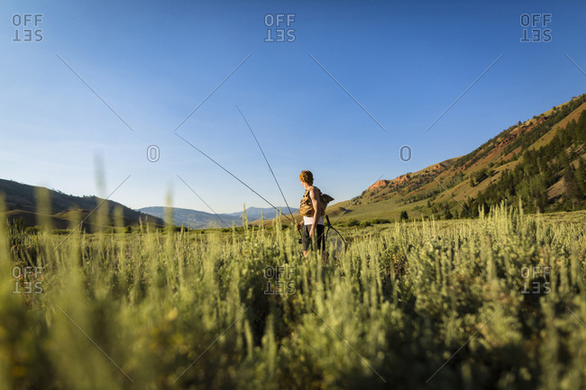 Teenage boy holding fishing rods while standing on field against clear sky