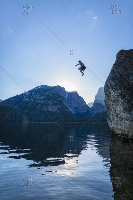 Low angle view of carefree teenage boy cliff jumping into river against sky