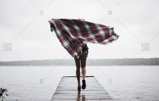 Rear view of carefree woman running with blanket on pier over Kawartha Lakes against clear sky
