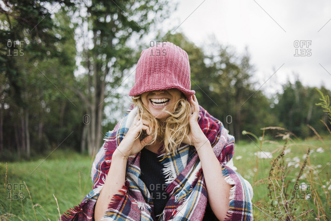 Cheerful woman covering eyes with knit hat while standing on field against trees