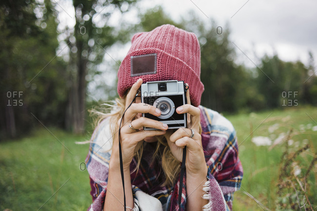 Woman photographing with instant camera on grassy field