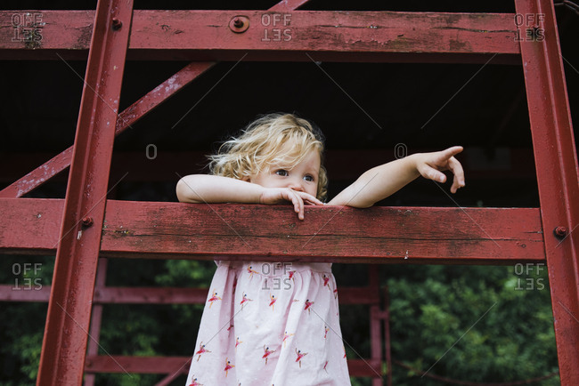 Cute girl looking away while standing in tree house