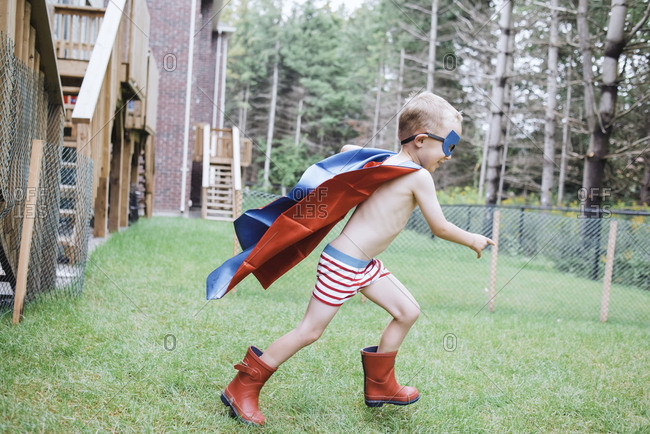 Side view of shirtless boy wearing cape and eye patch while playing in yard