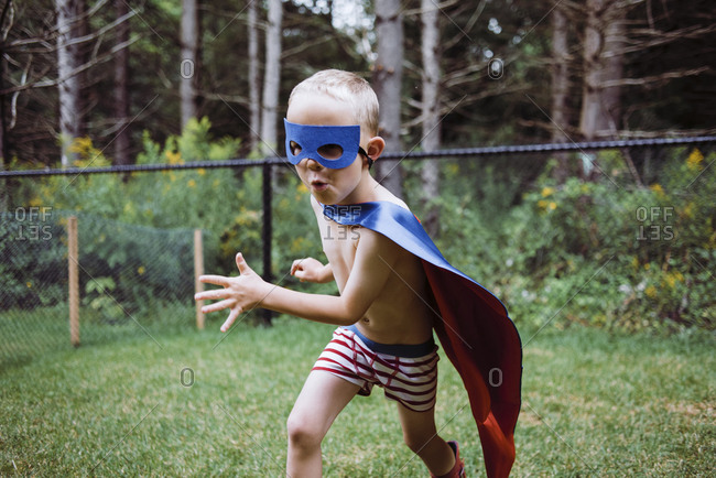 Playful shirtless boy wearing cape and eye patch while playing in yard
