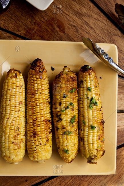 Overhead view of roasted corn cobs in plate on wooden table