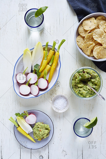 Overhead view of guacamole and vegetables on table