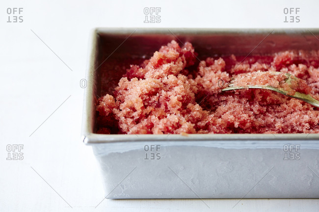 Close-up of hibiscus watermelon granita in container over white background