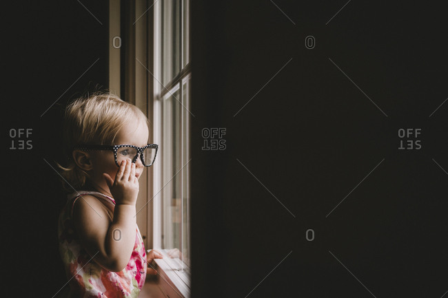 Baby girl wearing eyeglasses while looking through window