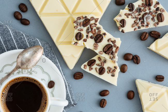 White chocolate triangles with coffee beans and cocoa beans served with coffee