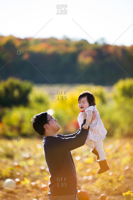 Father holding baby up in the air in a pumpkin patch