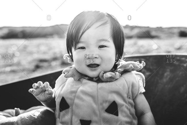 Baby dressed as a pumpkin sitting in a wheelbarrow in black and white