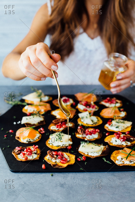 Woman drizzling honey on roasted sweet potato crostini