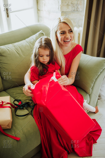 Little girl on mother's lap opening Christmas presents
