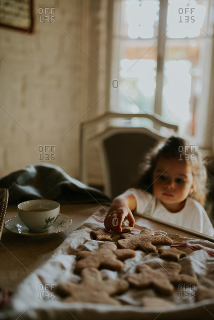 Girl reaching for gingerbread man cookie