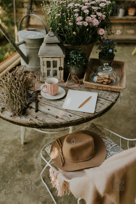 Hat on chair beside outdoor table with lantern, watering can and mums