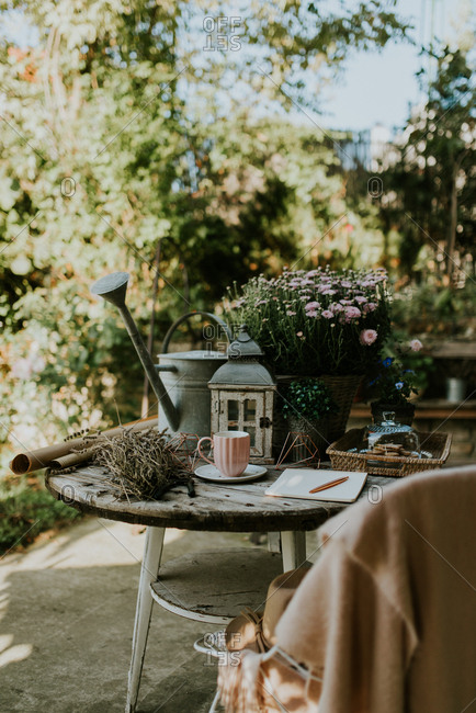 Outdoor table with lantern, watering can and mums