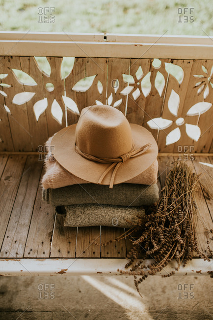 Hat on stack of folded blankets beside dried plants