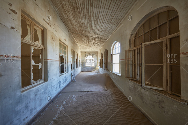 A view of a corridor in a derelict building full of sand