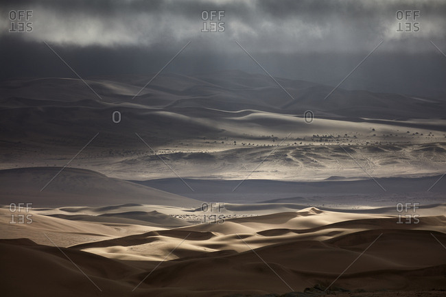 Sand dunes under a stormy sky
