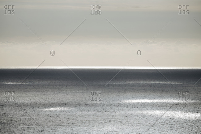 View from the land over the ocean, to the horizon in low light Sunlight patches on the water surface