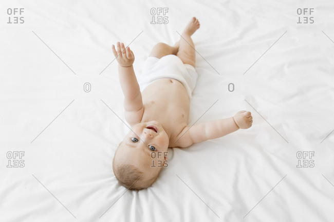 Overhead view of baby boy lying on his back on bed with white bedding, eyes wide open