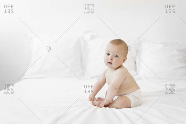 Baby boy sitting on a bed holding his toes, looking at the camera