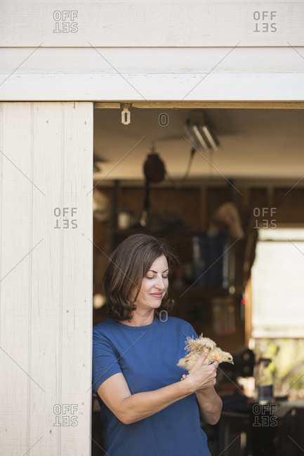 A woman holding a small fluffy chick, a baby bird in her two hands, standing at an open barn door