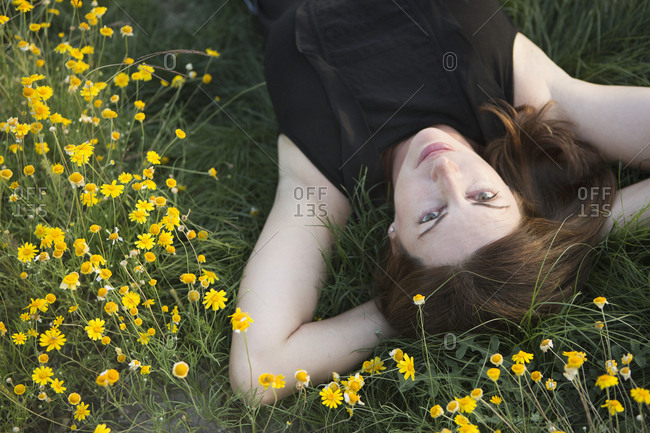 A woman in a black vest top and jeans lying on the grass with her hands behind her head